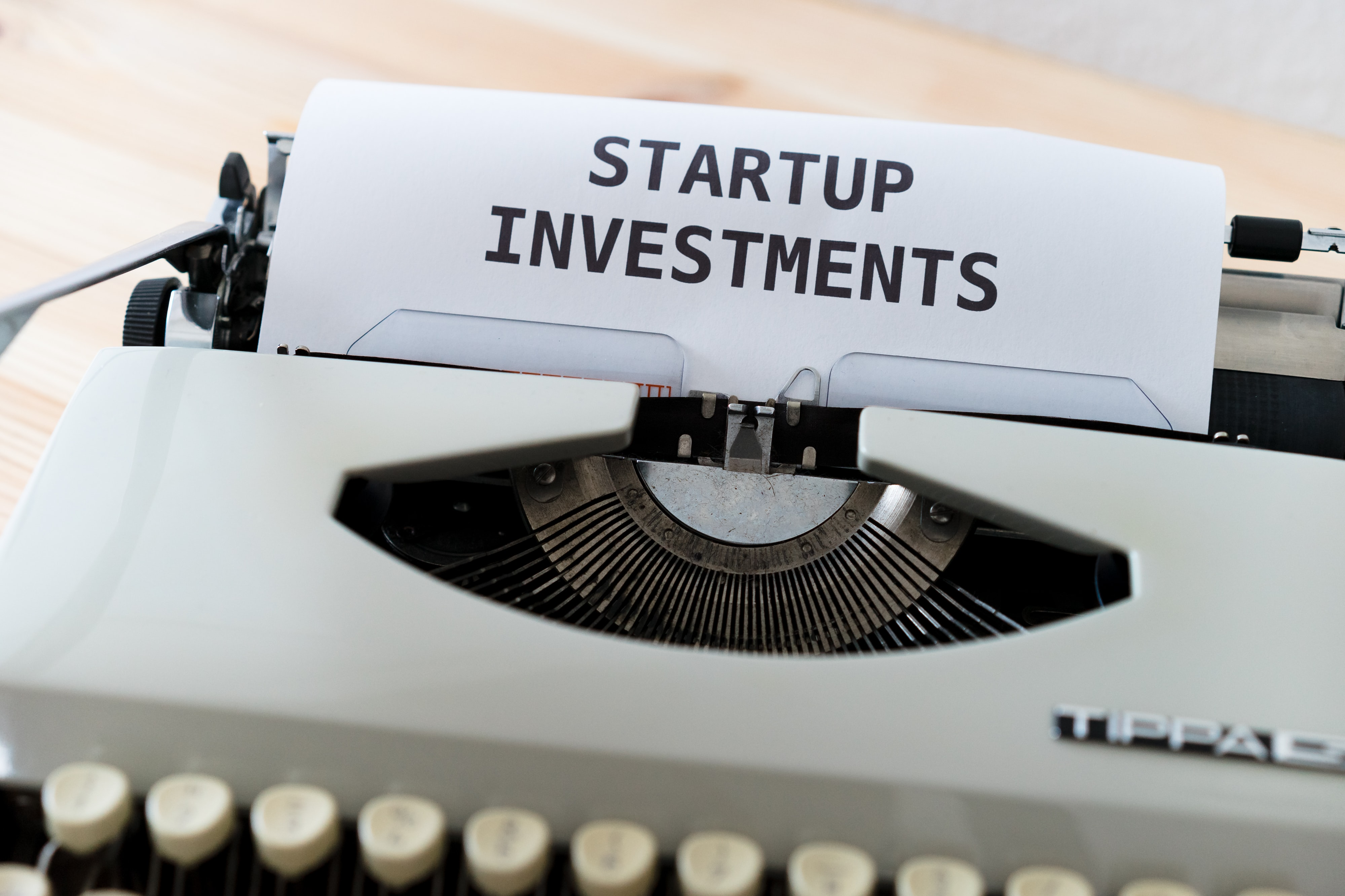 "A typewriter with the  words ""Startup Investments"" in capital letters typed on the paper"